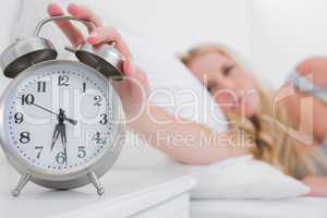 Tired woman turning off the alarm clock