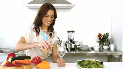 Woman pouring white wine in her glass