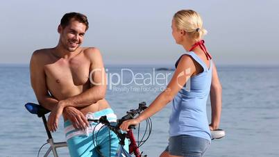 Two people speaking together on the beach