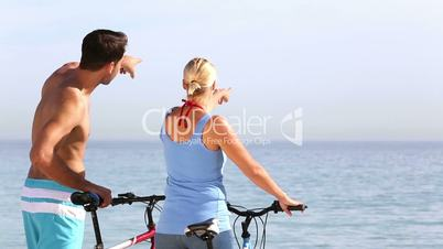 Man and woman pointing to the sea