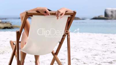 Woman sitting and tanning on a chair