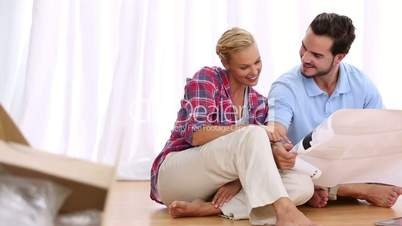 Couple at home sitting on floor
