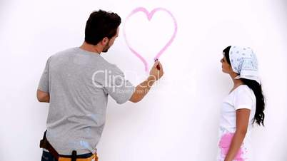 Attractive man painting a heart