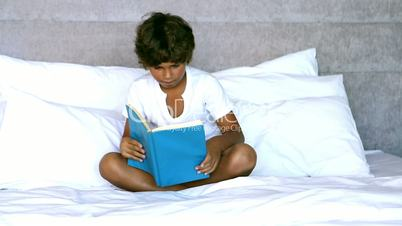 Child reading a book in bedroom