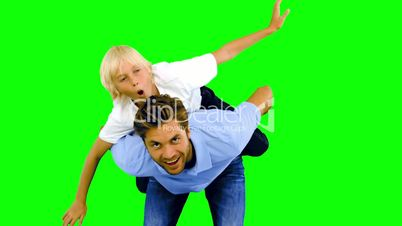 Son having a piggy back on his father on green screen