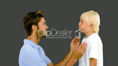 Man pressing inflated cheeks of his son on grey background