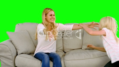 Daughter jumping in the arms of her mother in the sofa on green screen