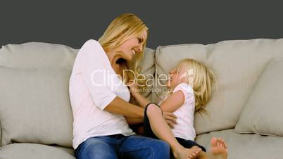 Mother tickling her daughter on sofa