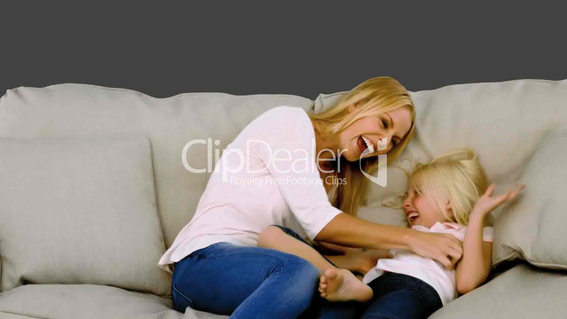 Mother Tickling Her Daughter On Sofa Royalty Free Video
