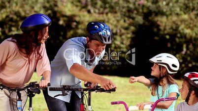 Parents and children pointing the way to go while they are riding bicycle