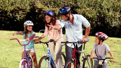 Parents showing the direction to children while they are riding bicycle