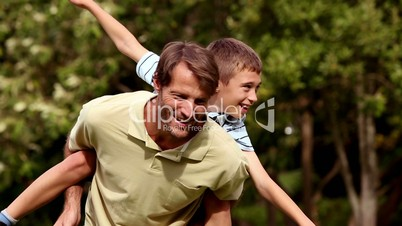 Father giving a piggy back to his son