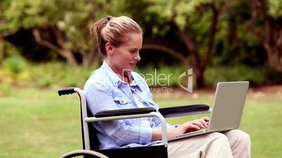 Attractive woman in a wheelchair using her laptop
