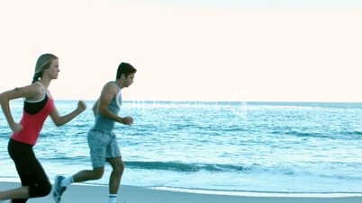 Two friends running on the beach