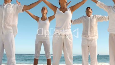Peaceful people practicing yoga the beach