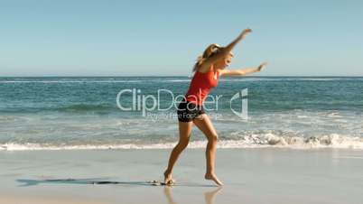 Attractive woman doing cartwheels on the beach