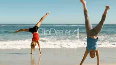 Attractive women doing cartwheels in front of the sea