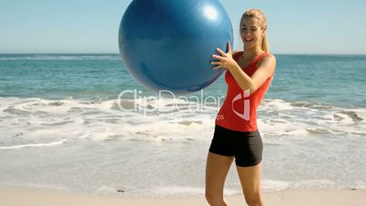 Happy woman playing with her fitness ball on the beach