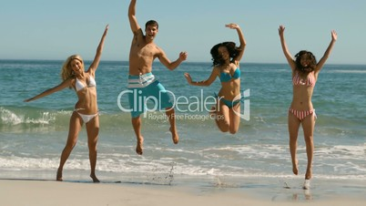 Young cheerful people jumping at the beach