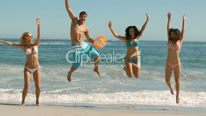 Happy friends jumping and playing on the beach