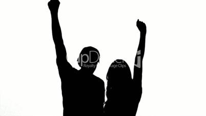 Silhouettes of couple raising their arms on white background