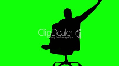 Silhouette of man turning of swivel chair on green screen