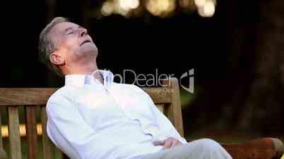 Elderly man sleeping on bench