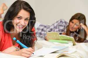 Smiling female students preparing for exam