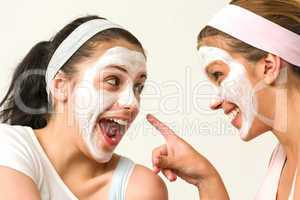 Two girls with cosmetic mask laughing