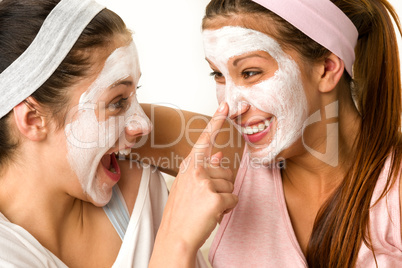 Playful teen wearing mask touches friend's nose