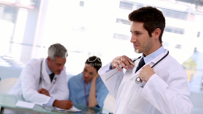 Smiling doctor putting stethoscope around his neck