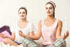 Meditating women wearing white facial mask