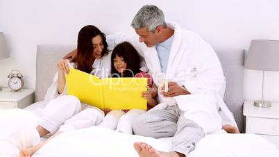 Parents and their daugher reading book
