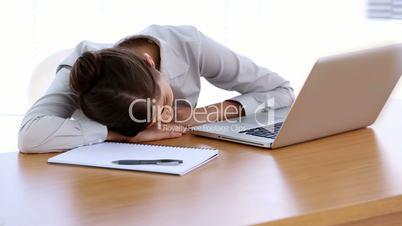 Businesswoman asleep on her desk