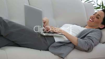 Businesswoman working lying down on a sofa