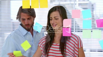 Creative team pointing adhesive notes