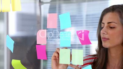 Woman writing on ahdesive note