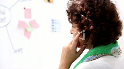 Thoughtful woman looking creative board