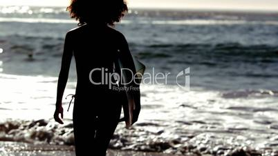 Silhouette of a woman running on the beach with her surfboard