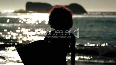 Silhouette of an attractive woman holding her surfboard