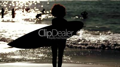 Silhouette of a woman holding surfboard on the beach