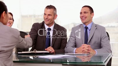 Job applicant shaking hands of business people