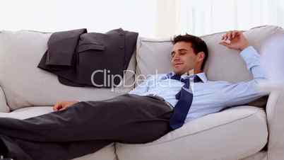 Smiling businessman lying on sofa