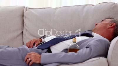 Alcoholic businessman lying and sleeping on sofa