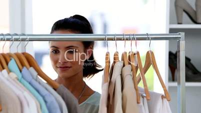 Smiling young woman choosing clothes