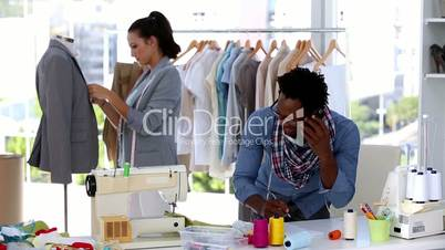 Fashion designer on the phone while discussing with a colleague