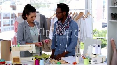 Fashion designers looking at thread spools