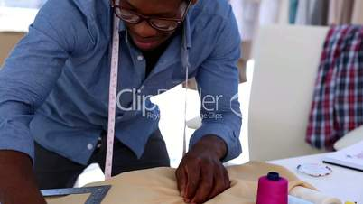 Fashion designer using a ruler on a fabric