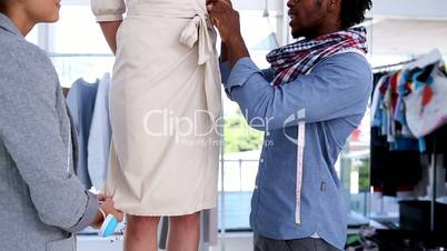Fashion designers working on the belt of a dress