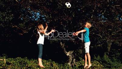 Siblings having fun with a football on a trampoline